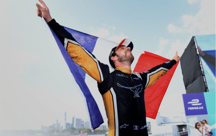 Newly-crowned Formula E champion Jean-Eric Vergne holding the French flag aloft against the backdrop of the New York skyline (a)